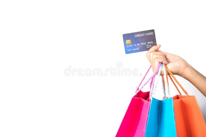 Mão da mulher com sacos de compras e cartão de crédito no backgroun branco imagem de stock