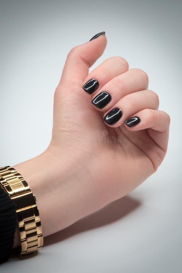 Mão da mulher com tratamento de mãos bonito no fundo branco Disponível um bracelete do ouro fotografia de stock royalty free