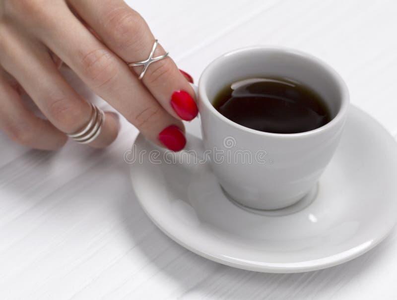 A m?o da mulher com um tratamento de m?os bonito que guarda um copo do caf? imagens de stock