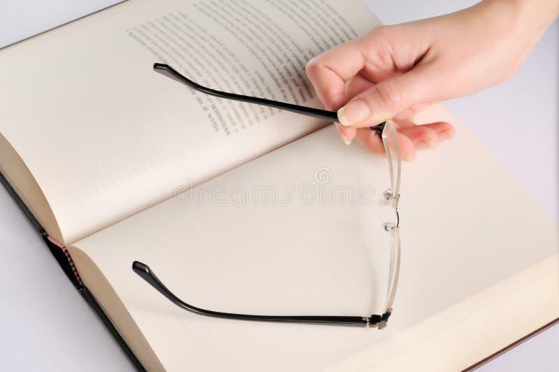 Mão da mulher com vidros no livro fotos de stock