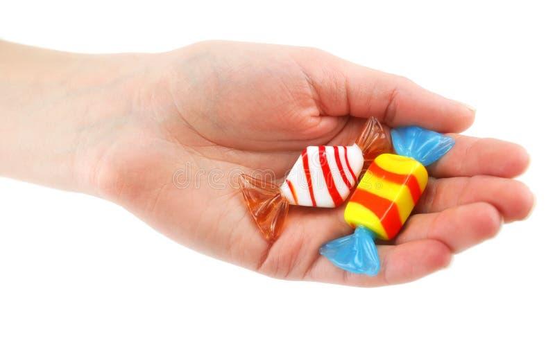 A mão da mulher dá doces coloridos dois imagem de stock royalty free