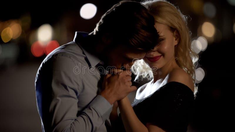 A mão da mulher de beijo masculina considerável maciamente, homem que seduz o louro bonito, data imagens de stock royalty free