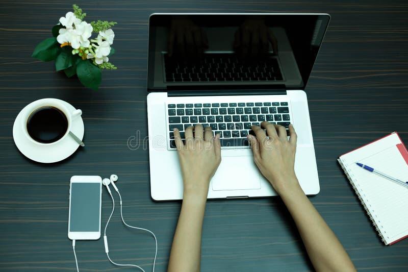 Mão da mulher de negócio no laptop e no telefone celular fotos de stock royalty free