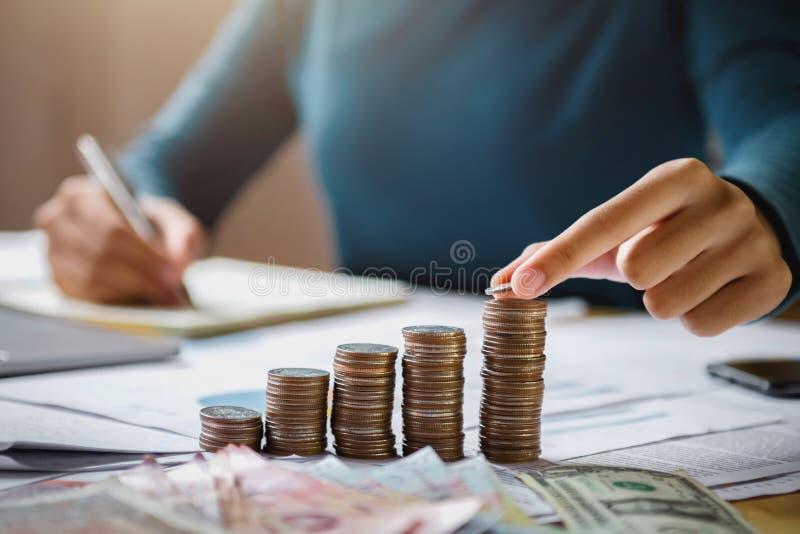 mão da mulher de negócio que guarda moedas para empilhar na finança de salvamento do dinheiro do conceito da mesa imagem de stock royalty free