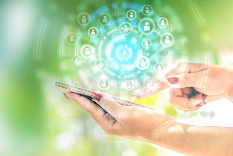 Mão da mulher de negócio que guarda o telefone esperto com ícone social da conexão, tecnologia com conceito dos trabalhos de equi imagem de stock royalty free