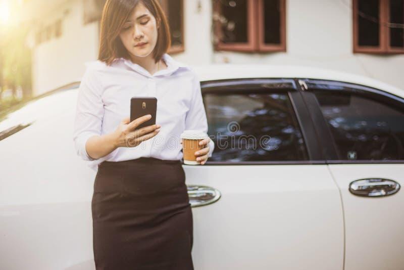 Mão da mulher de negócio que guarda um copo de café para levar embora e que olha os planos no smartphone imagens de stock royalty free