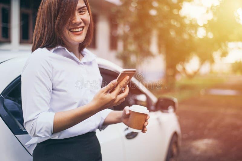 Mão da mulher de negócio que guarda um copo de café para levar embora e que olha os planos no smartphone fotografia de stock