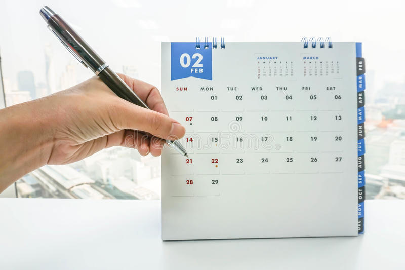 Mão da mulher de negócios com a nota da pena que encontra em fevereiro o calendário imagem de stock