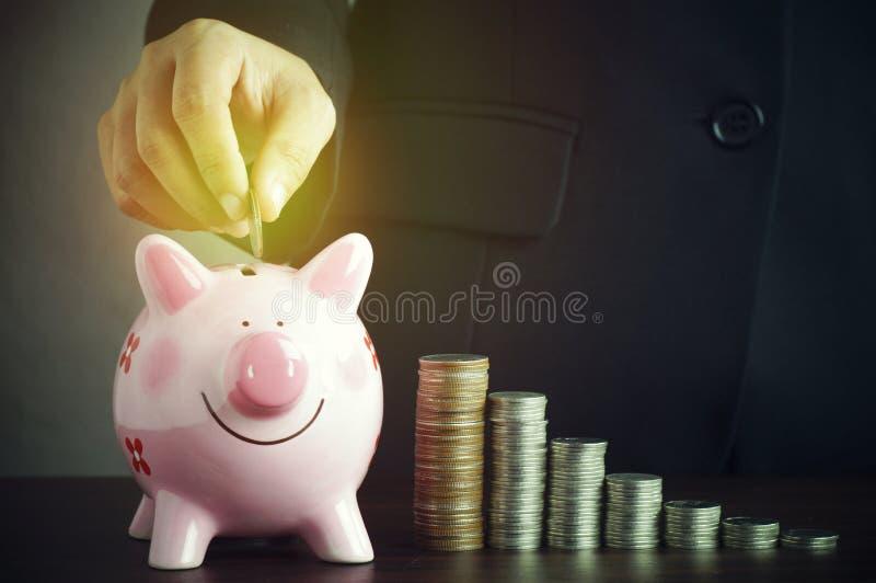 a mão da mulher de negócios pôs o dinheiro sobre o rosa do mealheiro imagens de stock