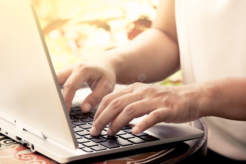 Mão da mulher de negócios que datilografa no teclado do portátil na cafetaria imagem de stock