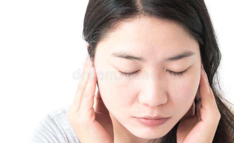 A mão da mulher do close up fecha suas orelhas com fundo branco fotos de stock royalty free