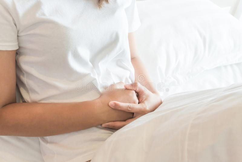 Mão da mulher do close up que guarda abdominal com a dor de estômago que encontra-se sobre foto de stock royalty free