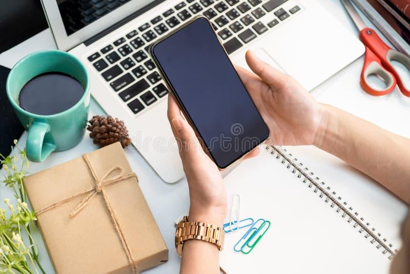 Mão da mulher do escritório que guarda e que olha o smartphone na tabela branca, mesa e portátil branco, smartphone, copo de café imagem de stock