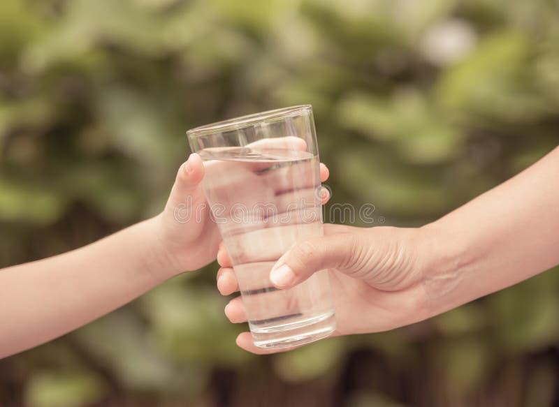 Mão da mulher do vintage do close up que dá o vidro da água fresca à criança fotografia de stock