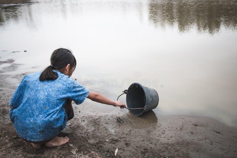 A mão da mulher está escavando a água em terra rachada imagens de stock royalty free