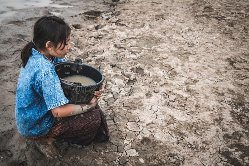 A mão da mulher está escavando a água em terra rachada fotografia de stock