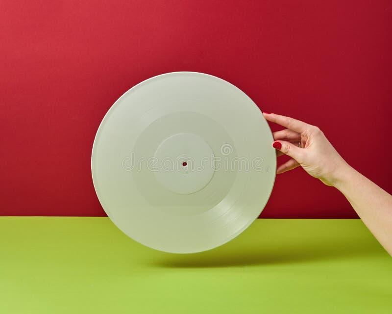 A mão da mulher está guardando um registro audio do vinil branco em um fundo verde vermelho do duotone com um espaço da cópia imagem de stock
