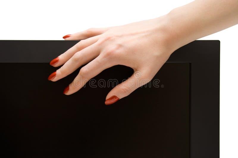 Mão da mulher na tela lcd-tevê imagens de stock