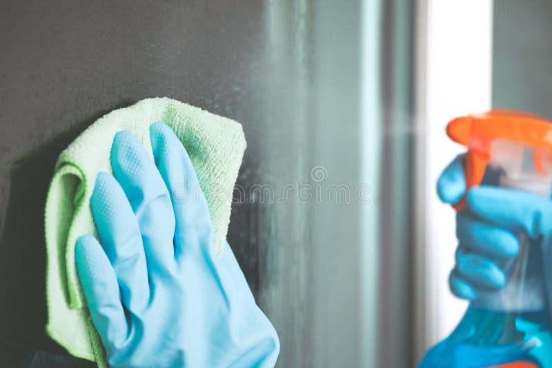 Mão da mulher nas luvas que limpam a janela fotografia de stock royalty free