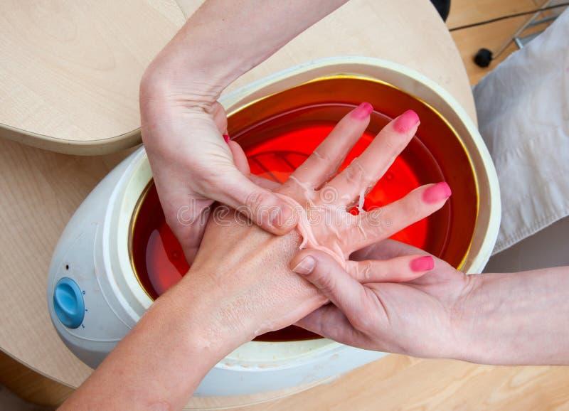 Mão da mulher no banho da parafina imagens de stock
