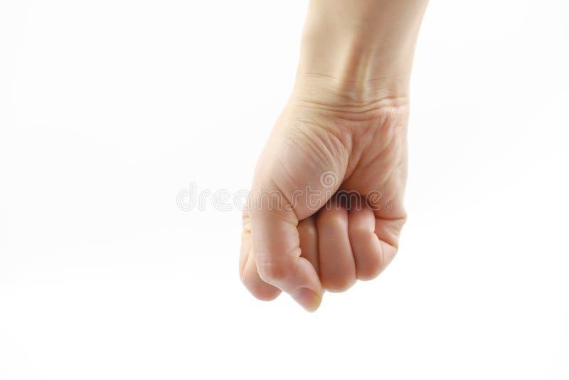 Mão da mulher no punho apertado do fundo branco fotos de stock