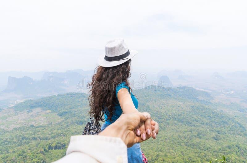 A mão da mulher da posse do homem, par do turista com a trouxa na opinião traseira da parte traseira da parte superior da montanh fotos de stock