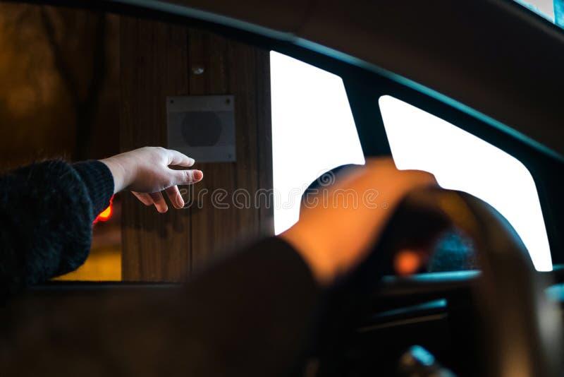 Mão da mulher que alcança o botão na movimentação completamente para pedir o fast food Humano no assento de motoristas que pede n imagens de stock