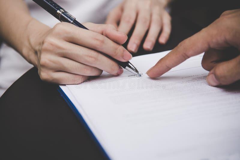 Mão da mulher que assina um contrato para a casa de construção com homem do arquiteto fotos de stock