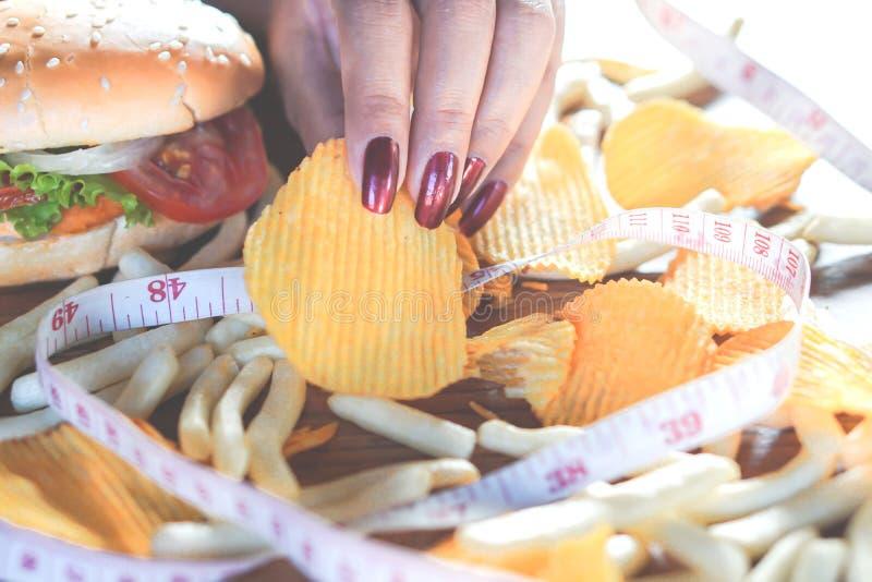 Mão da mulher que come o hamburguer do fast food, as microplaquetas de batata, as batatas fritas e a bebida doce na tabela de mad fotografia de stock