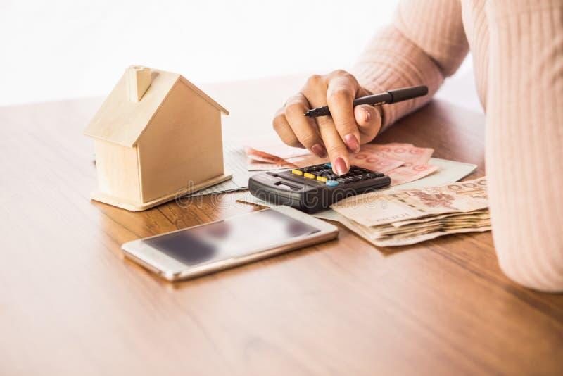 Mão da mulher que conta a moeda de papel do dinheiro com telefone, modelo da casa e a calculadora espertos na mesa, aplanando par imagens de stock