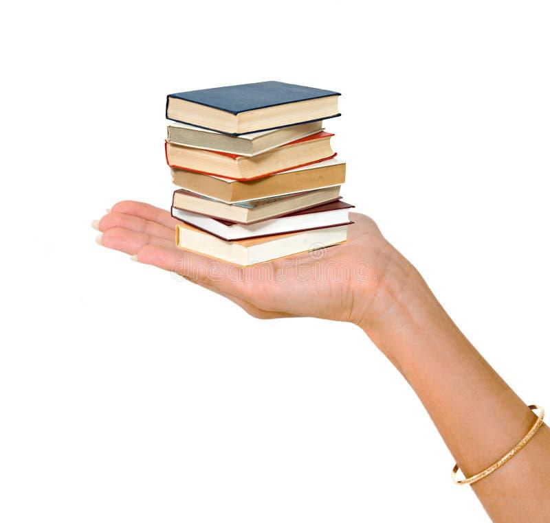 Mão da mulher que dá a pilha do livro foto de stock