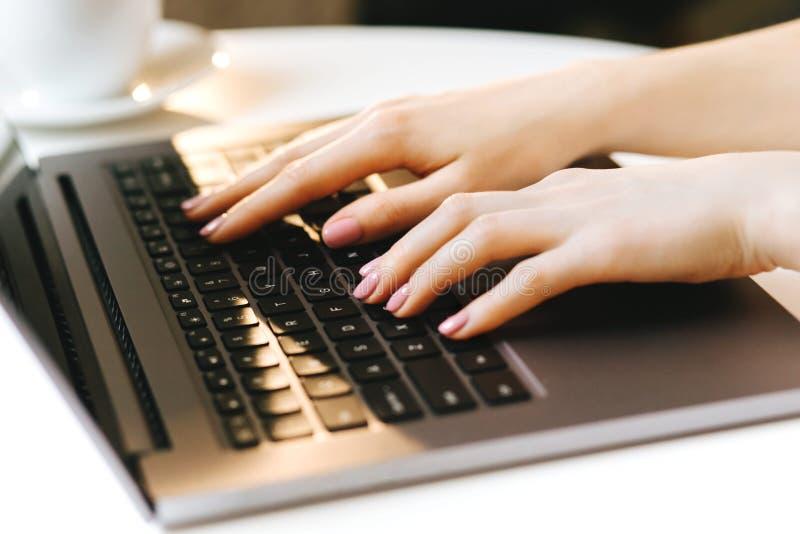 Mão da mulher que datilografa no teclado do portátil foto de stock royalty free