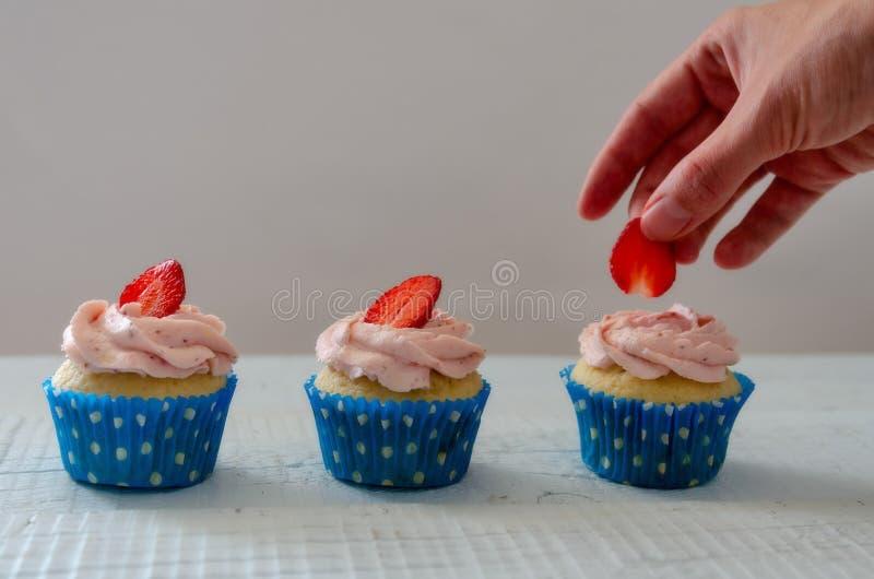 A mão da mulher que decora queques com branco das morangos fotografia de stock