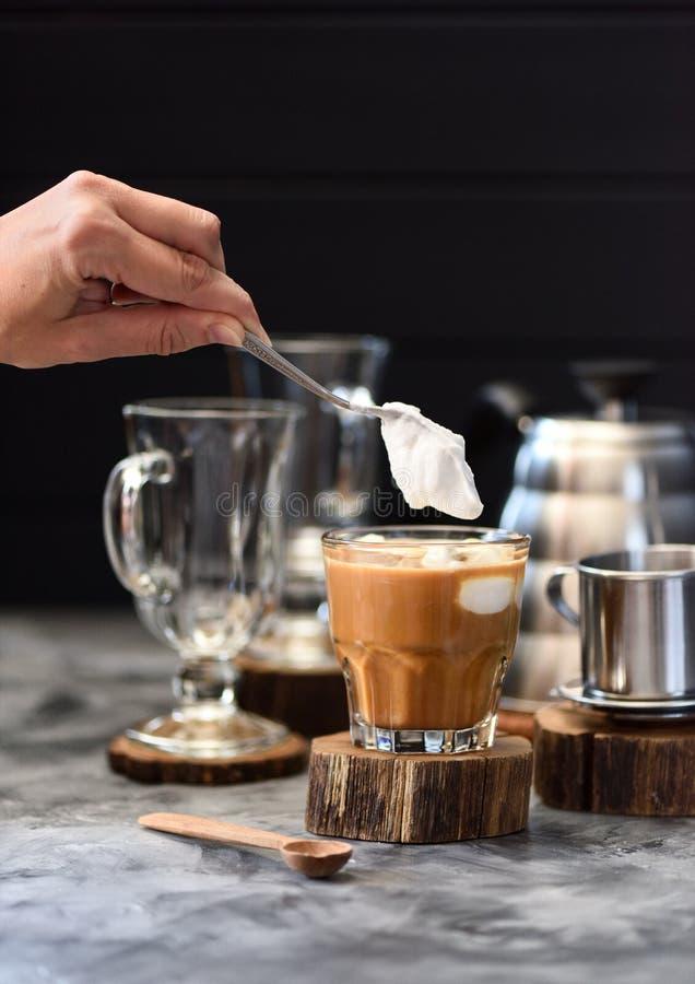 Mão da mulher que derrama o creme chicoteado do coco no café vietnamiano misturado do gotejamento no vidro no espaço escuro da có foto de stock royalty free