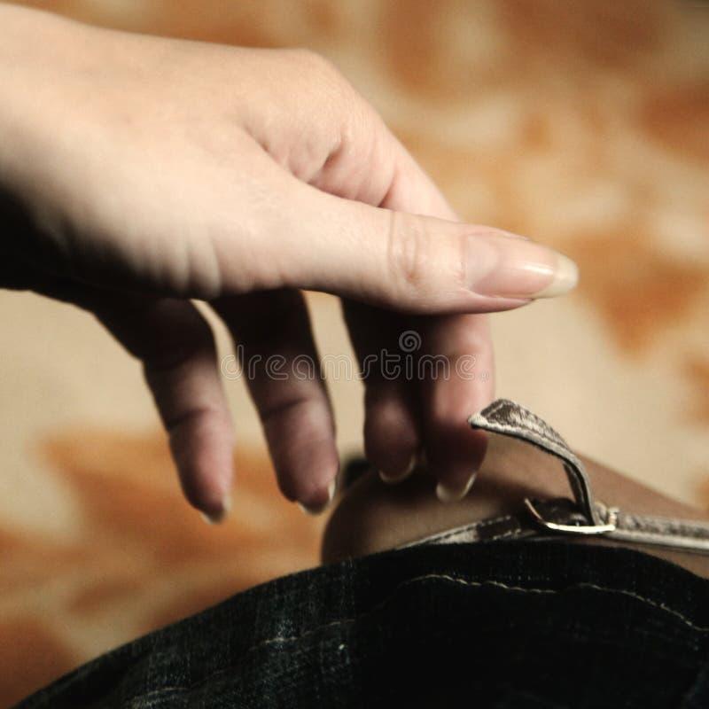 Mão da mulher que descola a sapata imagem de stock