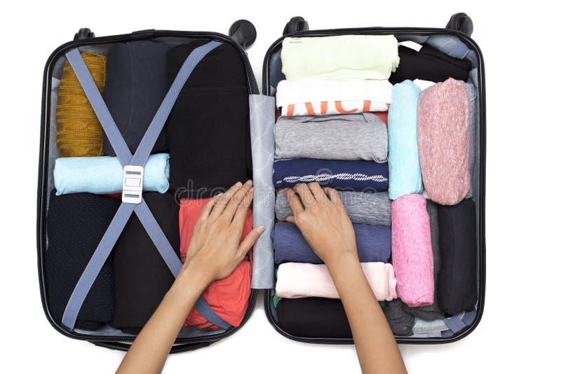 Mão da mulher que embala uma bagagem para uma viagem nova foto de stock