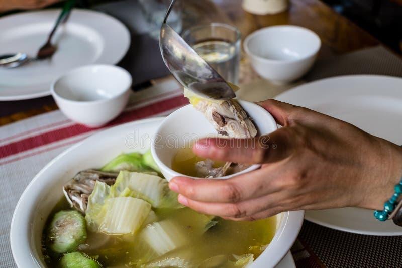 A mão da mulher que enche uma fatia de sopa dos peixes da palombeta em uma bacia pequena Peixes ou Jack da palombeta igualmente c fotos de stock
