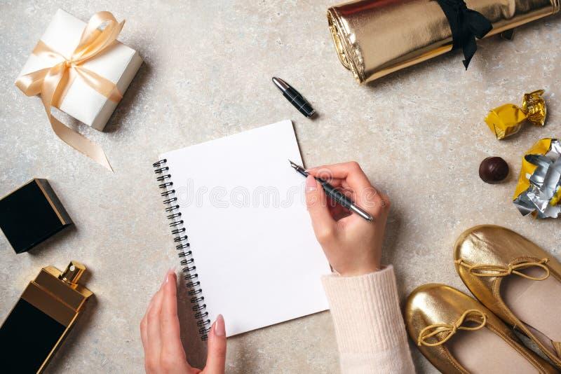 Mão da mulher que escreve a mensagem de texto no bloco de notas de papel vazio Tabela feminino com material elegante Mesa do espa imagens de stock royalty free