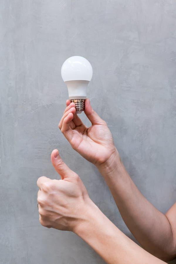 Mão da mulher que guarda a ampola do diodo emissor de luz do branco brandnew fotografia de stock royalty free