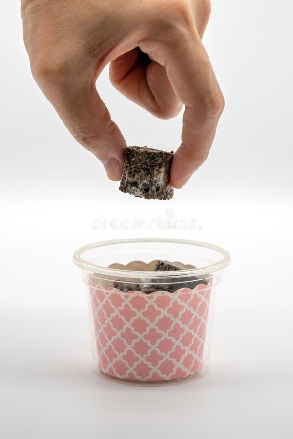 Mão da mulher que guarda a barra doce do marshmallow das cookies com o dedo dois fotos de stock