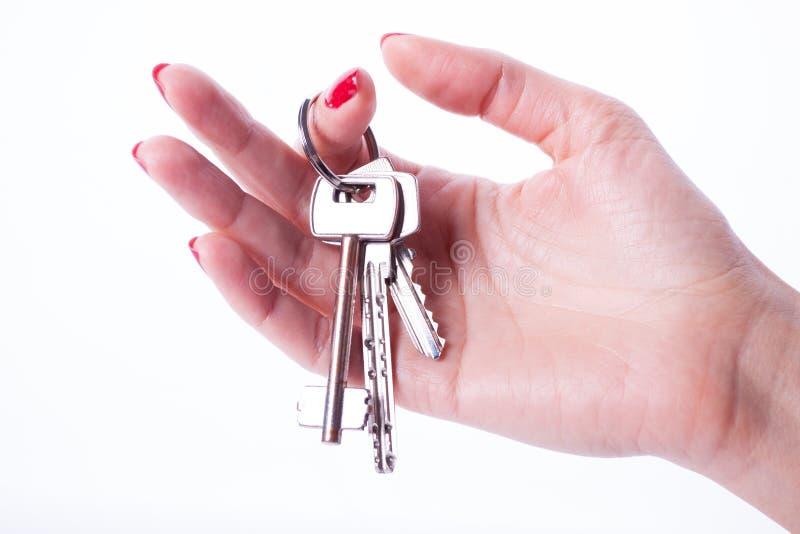 Mão da mulher que guarda chaves imagem de stock