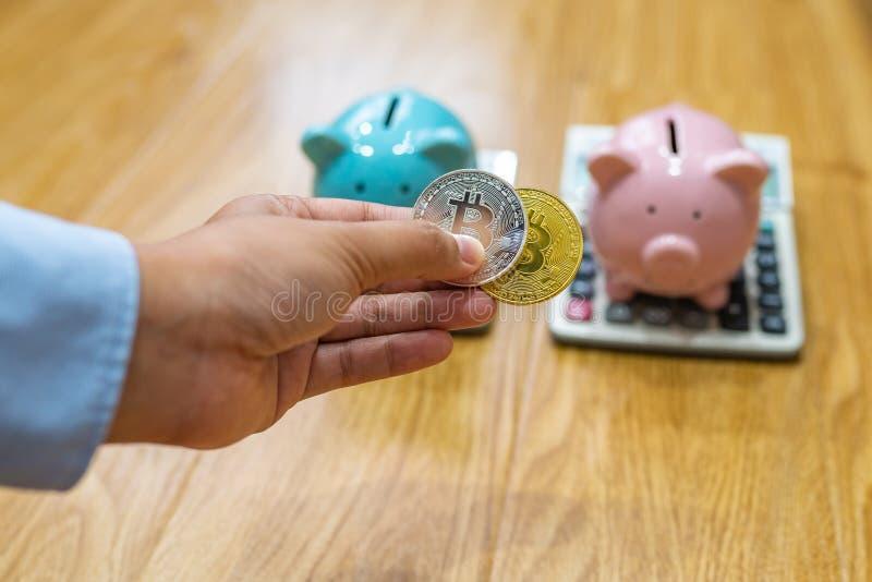 Mão da mulher que guarda dois bitcoins na frente do piggybank foto de stock royalty free