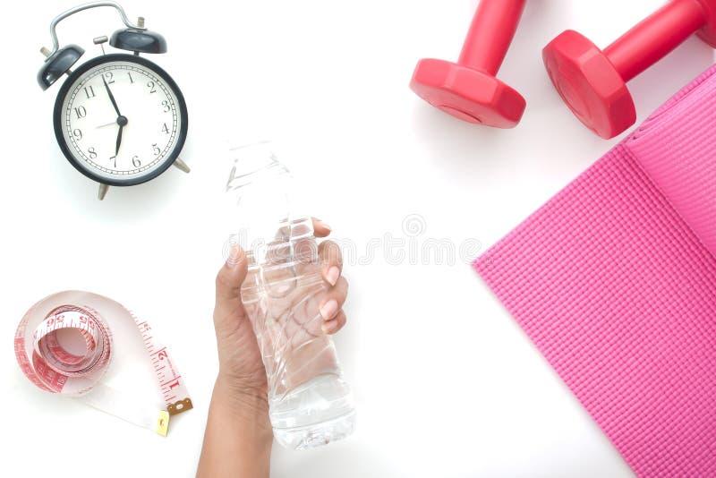 Mão da mulher que guarda a garrafa da água, do conceito saudável e da dieta isolados no branco fotos de stock