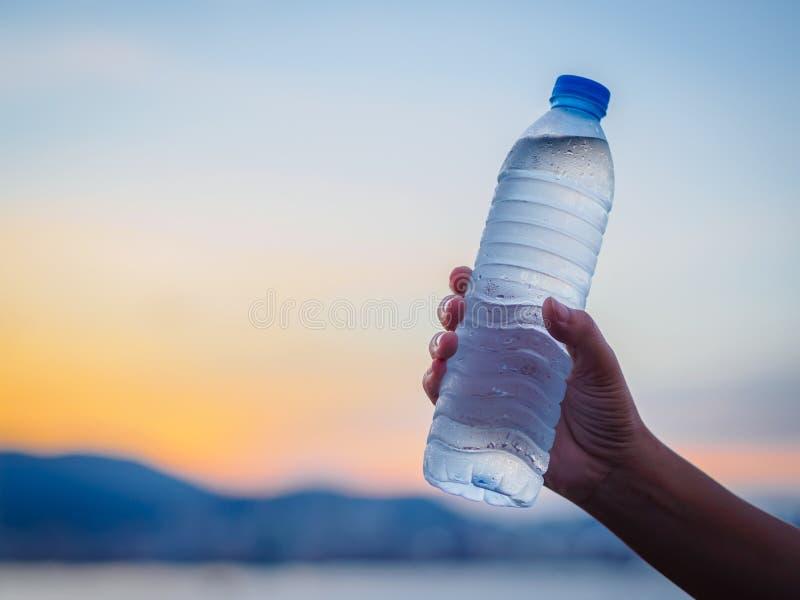 Mão da mulher que guarda a garrafa de água no fundo do céu do por do sol imagem de stock royalty free