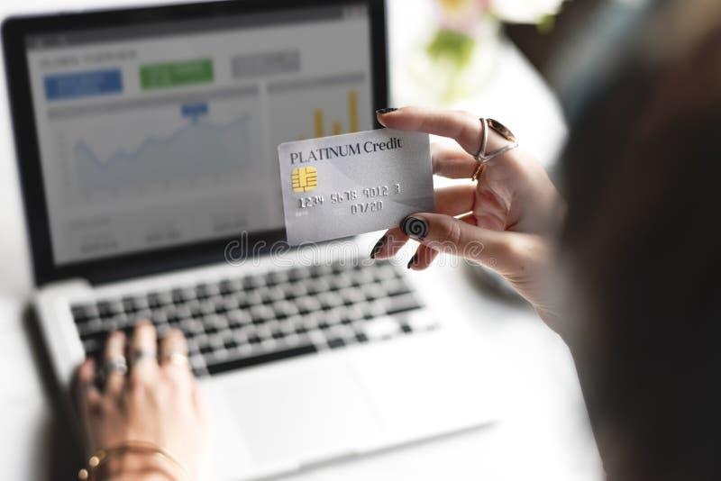 Mão da mulher que guarda o cartão de crédito da platina com fundo do portátil imagem de stock