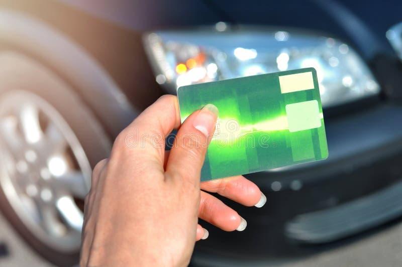 Mão da mulher que guarda o cartão de crédito verde usando-se para comprar um carro novo Auto negócio, conceito da venda imagens de stock