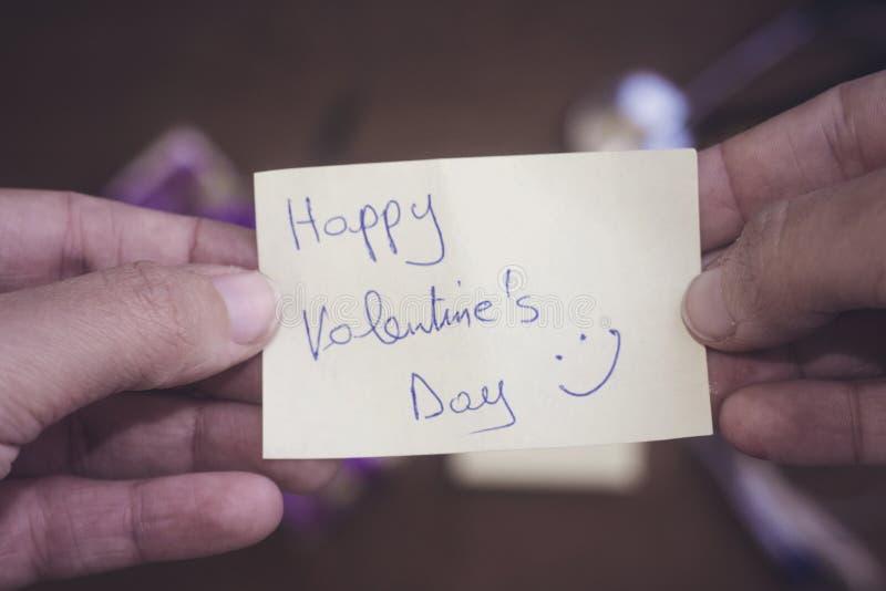 Mão da mulher que guarda o dia feliz do ` s do Valentim com o cartão de cara feliz fotografia de stock