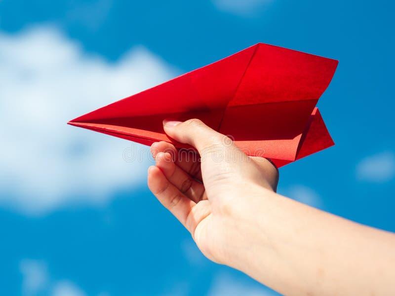Mão da mulher que guarda o foguete de papel vermelho com fundo do céu azul Conceito da liberdade fotografia de stock royalty free