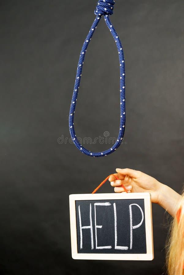 Mão da mulher que guarda o sinal da ajuda ao lado da corda imagem de stock
