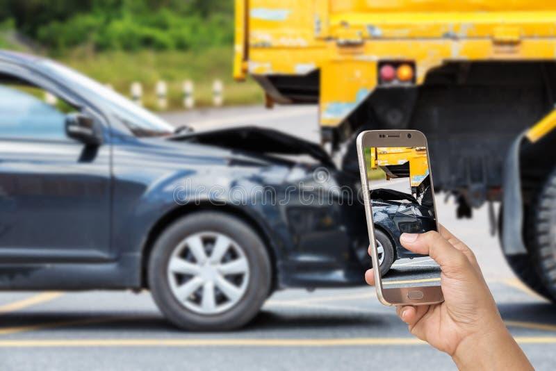 A mão da mulher que guarda o smartphone e toma a foto do acidente de trânsito imagem de stock